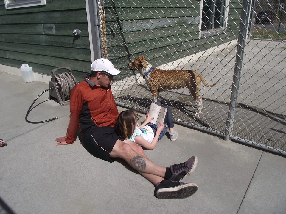 Man and child reading to a shelter dog