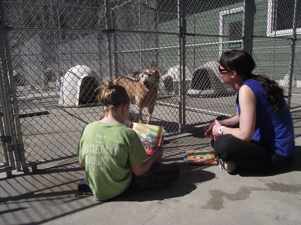 Young person and woman reading to a shelter dog