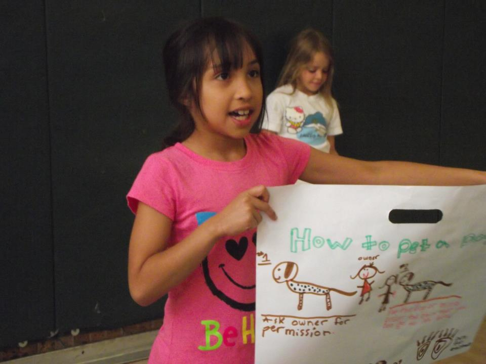 Little girl showing off her poster about dog safety and respect